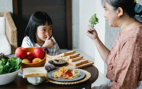 Smiling grandmother showing fresh leaf lettuce while sitting against cute Asian girl showing like gesture and looking at each other