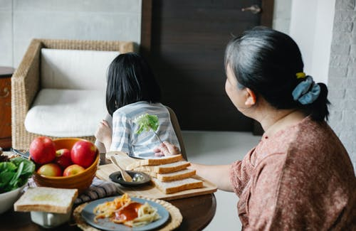 Unrecognizable grandmother showing fresh lettuce to hiding little girl while sitting at table with various food