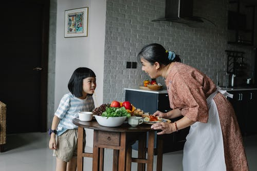 Happy woman with little girl preparing healthy lunch