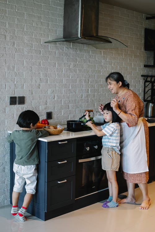 Elderly Asian woman in apron cooking on stove with help of preschool children while spending time at home
