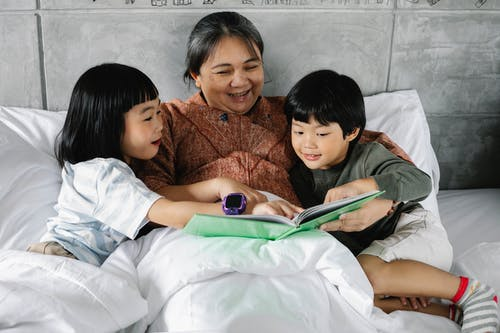 Happy ethnic woman and kids reading book together