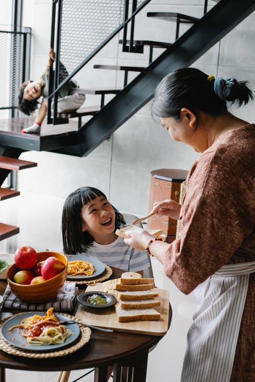 Elderly woman in apron preparing dinner with pasta and toasts for Asian children at home