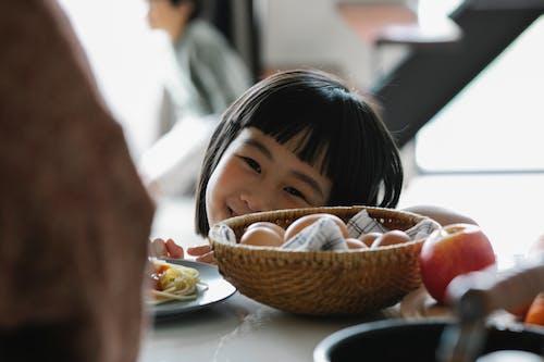 Happy Asian little girl in kitchen