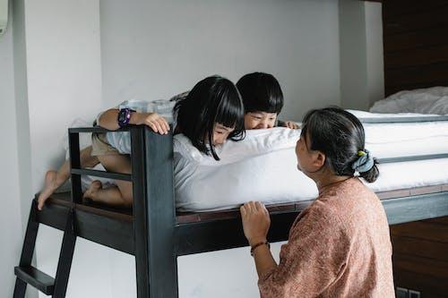 Senior Vrouw Spelen Met Kinderen Op Bed