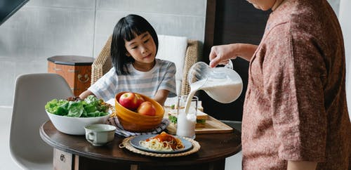 Crop faceless female standing near table and preparing healthy lunch for cute Asian kid at home