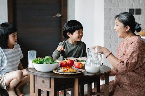 Asian woman having breakfast with cute children