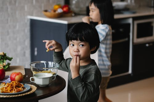 Cute Asian boy eating breakfast at table