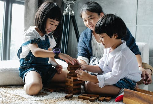 Full body of happy ethnic children sitting on floor and playing tower game while spending weekend with grandmother