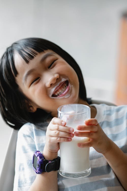 Cute little girl with smartwatch toothy smiling while holding glass of milk in hands