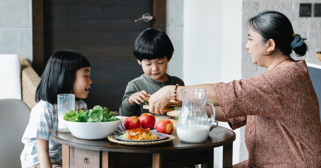 Grandmother having breakfast with Asian children