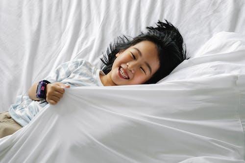 Happy Asian little girl lying on bed