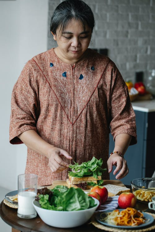 Asian senior woman cooking sandwich at home