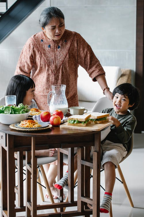 Elderly woman standing near table with various food while laughing children having lunch at home