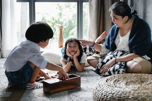 Ethnic woman spending time with children