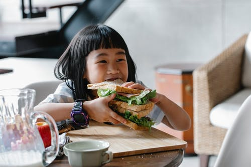 Asian child sitting at wooden table during breakfast and eating tasty sandwich with lettuce leaves