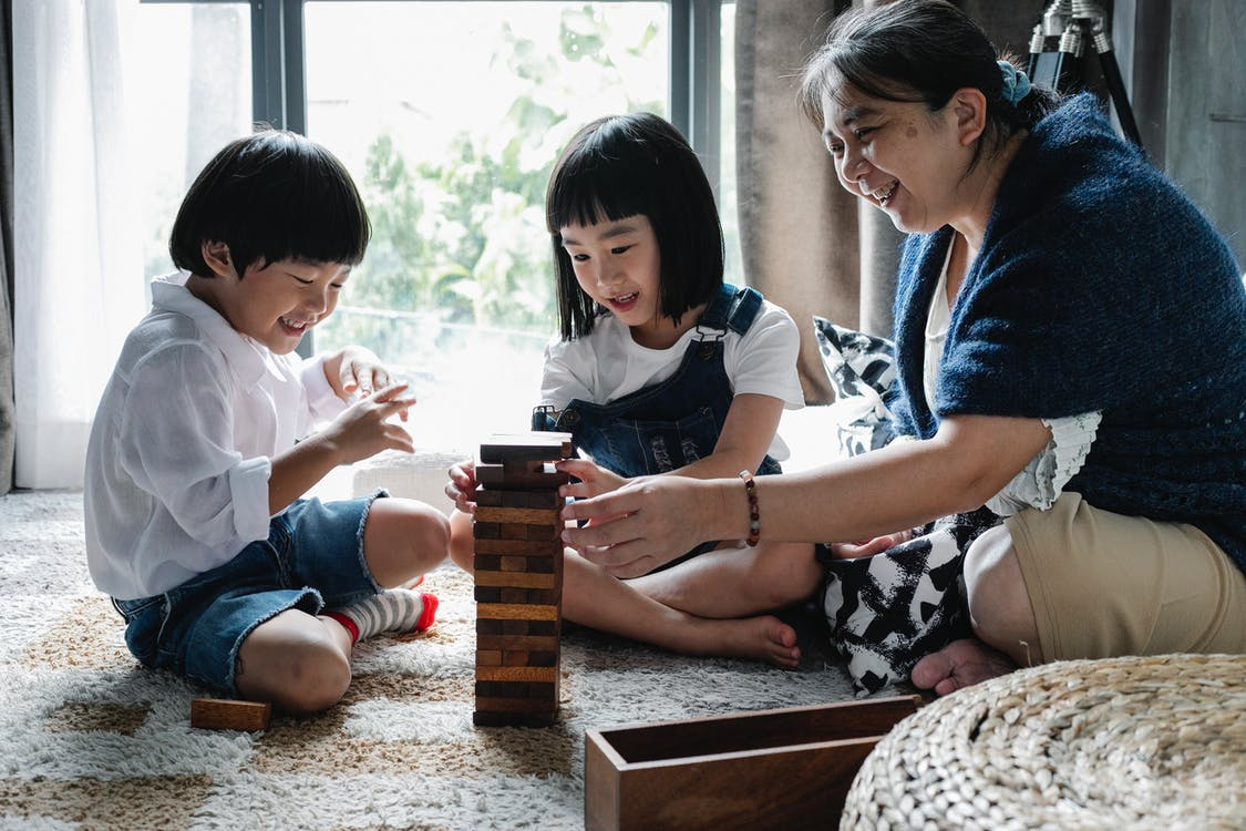 Full length of grandmother sitting on floor with crossed legs and playing tower game with children at home