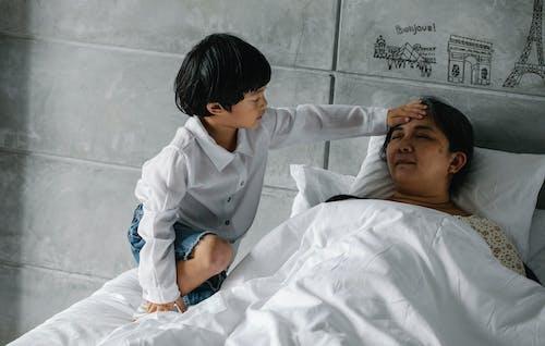 Little Asian boy measuring temperature of sleeping grandmother