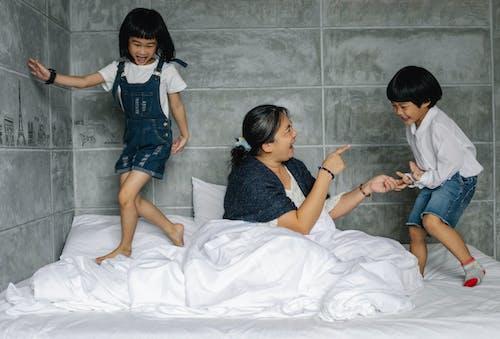 Vrolijke Oudere Vrouw Met Speelse Kinderen Op Bed