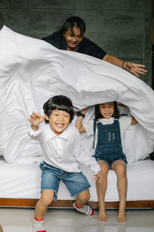 Full length of Asian children in casual clothes toothy smiling while playing with grandmother in bedroom