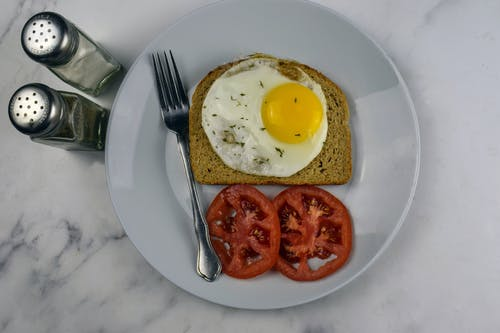 Egg and Fried Egg on White Ceramic Plate