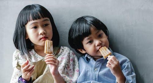 Adorable Asian kids enjoying sweet ice cream