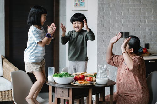 Joyful Asian grandmother and grandchildren wearing casual clothes having lunch and playing patty cake game in modern light living room