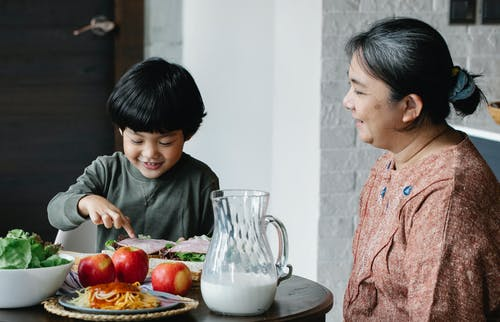 Happy Asian grandmother and grandson having lunch in kitchen