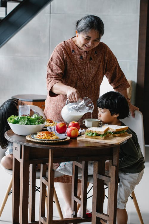 Smiling grandmother wearing casual clothes pouring fresh milk for little boy while gathering together at round table for tasty lunch