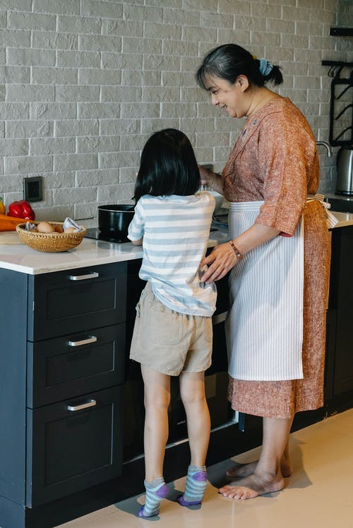 Smiling Asian grandmother teaching little granddaughter to cook