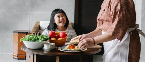Joyful Asian girl and granny gathering at table for lunch