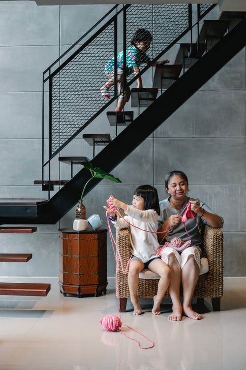 Full body content Asian granny and girl sitting on chair and knitting near adorable boy climbing upstairs in modern living room