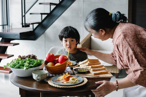 Adorable Asian boy eating pasta near attentive granny in kitchen