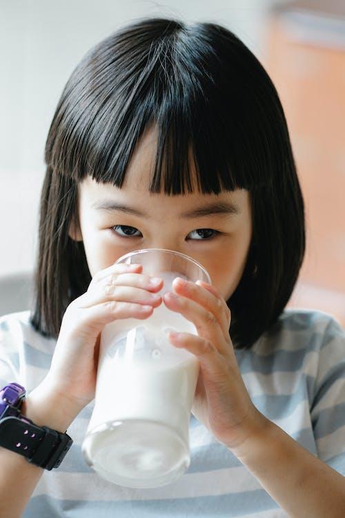 Nettes Asiatisches Mädchen, Das Milch Vom Glas Trinkt