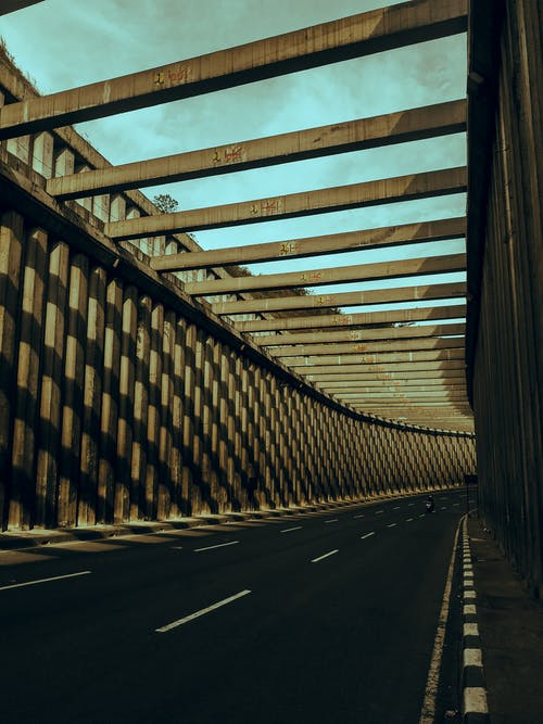 Asphalt roadway between geometric cement fence under beams and sky with clouds in town