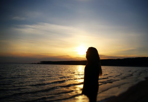 Side view female silhouette standing on rippling waving seacoast and looking away in dreams at picturesque sunset