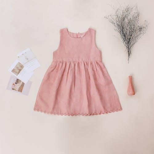 女孩的時髦禮服在米黃背景的明信片附近