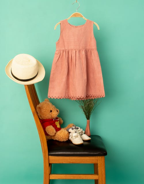 Stylish clothes on hanger above hat and shoes with soft bear on chair near bright wall