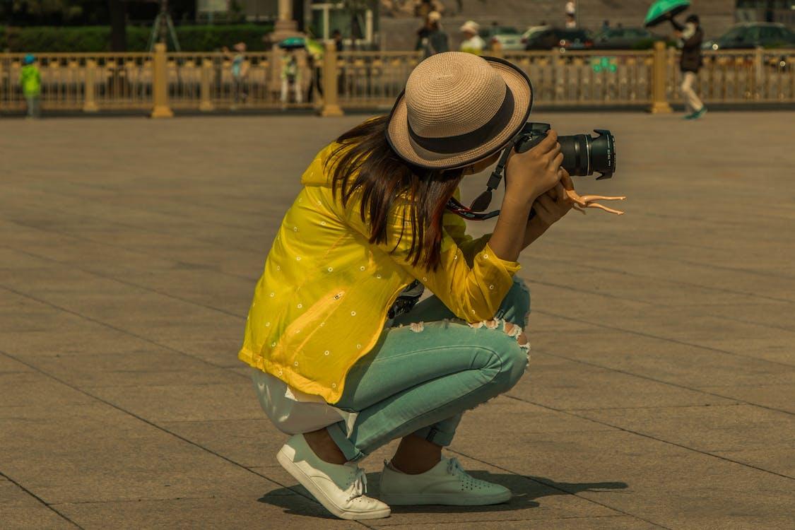 Woman Sitting on Pavement While Taking Photo