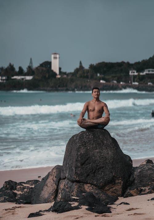 Young ethnic man practicing yoga sitting on boulder on sandy seashore