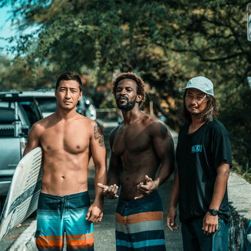 Confident fit young diverse male travelers in swimwear standing on street near green tree with surfboard in hand and looking at camera