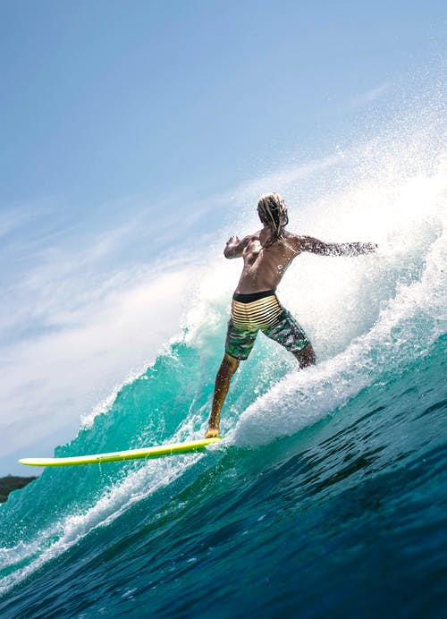 Back view of faceless muscular young male surfer in swimwear riding splashing waves in turquoise ocean during summer holidays on sunny day