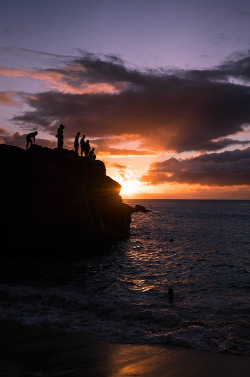 Anonymous people enjoying sunset over sea from rocky cliff
