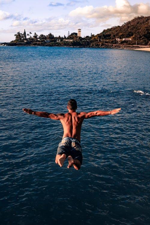 Monter Le Jeune Homme Sautant Dans L'océan