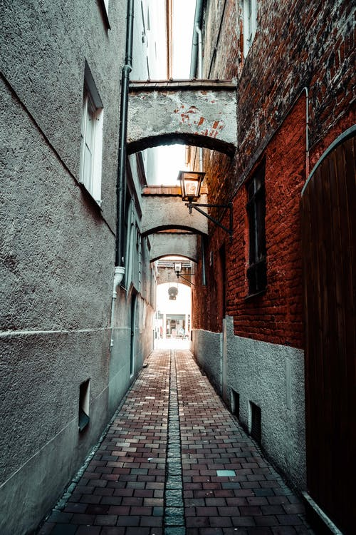 Narrow paved walkway between brick and stone buildings in old city in daylight