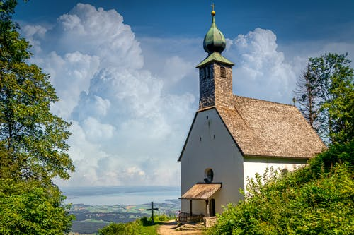 White and Brown Church Near Green Trees Under White Clouds and Blue Sky