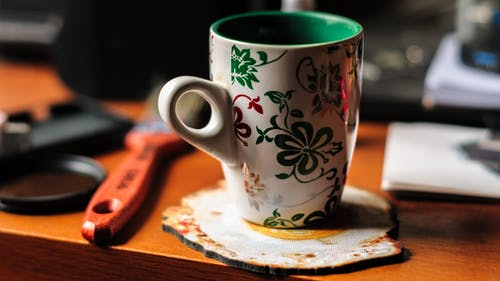 Cup with green and red ornaments on wooden table in daytime on blurred background