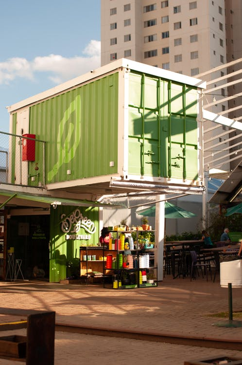 Simple green container house next to tall multistory building in city in daytime