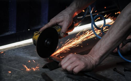Crop unrecognizable male using angle grinder and cutting metal piece while working in garage