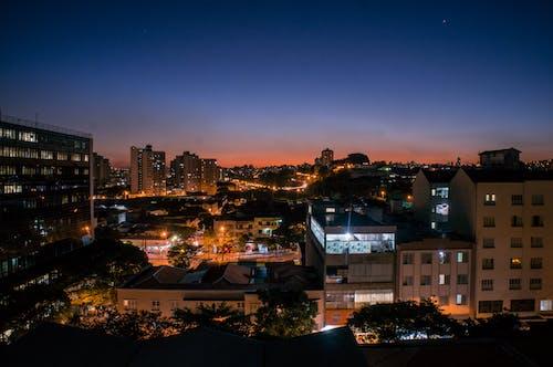Cityscape with illumination under sunset sky