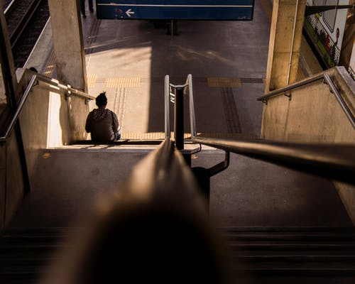 Woman sitting on stair in railway station